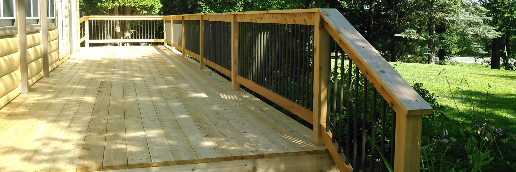 Newly constructed cedar wood deck with wrought iron railings